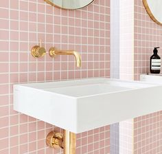 Pale pink square bathroom tiles and gold taps
