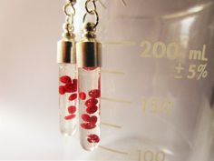 The tiny red blood cells are hand sculpted of polymer clay in the classic donut shape, then suspended in clear resin inside a test tube or fang shaped glass vial. These earrings are perfect for people in the medical field such as doctors and nurses, scientists or microbiologists, hematologists, professors, biology/pre-med students, etc. Great for vampire, horror, goth, and gore fans too! The vials are approximately 1 1/2 inches long with caps permanently secured in place. Please understand…