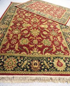 "Two Persian Empire oriental style rugs brightly colored. Predominantly red with black border and greens and golds in design. No spots or stains. Nylon. 7'10""x 10'10"" and 5.5'x8'"