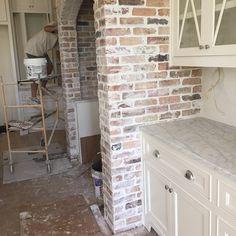 White cabinets. Marble countertops. Love the brick around the stove area.