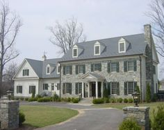 Stone and clapboard are an elegant pairing, complete with circular drive