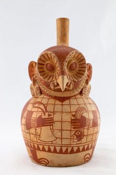 Moche ceramic vessel from Pre-Columbian Peru, generally interpreted as an anthropomorphic owl, though it could also be a costumed priest or a possessed shaman.  In the figure's right hand is a tumi knife.  In the left is a decapitated head, held by the hair.  /NSC