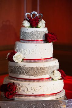 Four-tier white wedding cake with white fondant, silver beads, rhinestones, red ribbons and fresh red and white roses Red Silver Wedding, Silver Wedding Decorations, Wedding Cake Red, Quince Decorations, Fiesta Decorations, Themed Wedding Cakes, Wedding Cake Designs, Wedding Ideas, Quinceanera Cakes