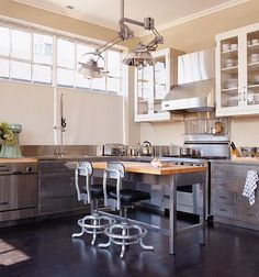 Salvage industrial finds in this kitchen include a dentists lamp, drafting stools, a shop table, and vintage stainless steel cabinets reclaimed from a lab.