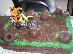 Dirt Bike Chocolate cake with chocolate frosting. I cut Twinkies in half and frosted over for the mounds. Dirt is chocolate graham cracker...