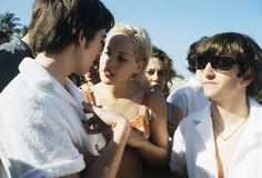 Two of the Beatles, George Harrison, left, and Ringo Starr, right, at the beach in Miami, Florida, in February of 1964. Others are unidentif...