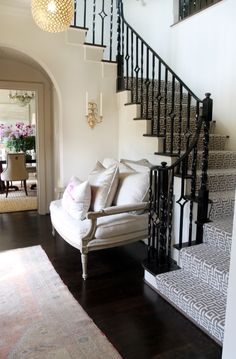 Gorgeous foyer with arched doorways and glossy black iron staircase spindles and staircase banister. Staircase with gray geometric Greek key pattern stair runner. French settee in foyer and French wall sconces.