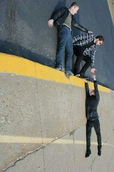 Cool photo, it looks like the guy is dangling off the edge of a building with his friends trying to help him!