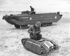Member of the US Navys Second Beach Battalion examining a German SdKfz 302 Goliath remote-controlled mine (called Beetles by US forces) on Utah Beach 11 June 1944. Note DUKW in the background.