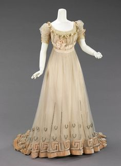Evening Dress 1905-07 The dress also incorporates signature decorative techniques such as velvet piping outlining peach satin ribbon at neckline and waist and the contrasting tones and reflections of silver, satin and velvet