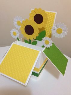 Handmade Card in a box. This style of card is very popular now a days. Bright yellow and green colours makes it perfect to bring a smile to the recipients face. All the flowers are individually made by me and It makes a nice virtual bouquet card for someone special. This Card comes as flat with an envelope about 15cm X 15cm. When you open the card it opens like like a pop up card in a box and sits like shown in the photo above. There is a blank panel in the back about 6.5cm X 14.5cm to write…