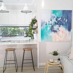 Modern contemporary scandinavian Australian kitchen in white with window splashback and vertical garden shelves. Original artwork by Kate Fisher Art. Kmart stools. Mocka side table.
