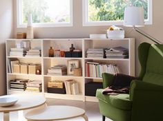 A basement living room with three low BILLY bookcases in white and a STRANDMON wing chair in green.