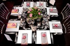 Elegant table settings.  Dark/black linen with white plates, silver napkins & pinks flowers. But with blue flowers.