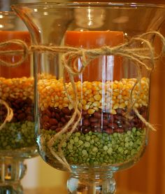 Fall Hurricane Vases:  corn kernels, small red beans, split peas, black beans, White Northern Beans and Red Lentils. Place the candle in empty hurricane, then begin pouring beans very slowly around candle to desired level. Repeat layers with different beans. Tie fun ribbon or let stand alone! Hurricane Candle, Hurricane Centerpiece, Candle Centerpieces For Home, Candle Vases, Candle Decorations, Autumn Centerpieces, Easy Decorations, Decoration Noel, Shower Centerpieces