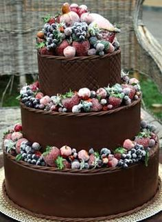 Big three tier, rich chocolate wedding cake covered with fresh berry fruits, sprinkled with white icing suar