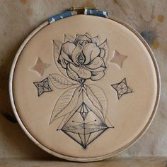 """Geometric magnolia circle"". Punctured Artefact. Tattooed leather, edition of 6."