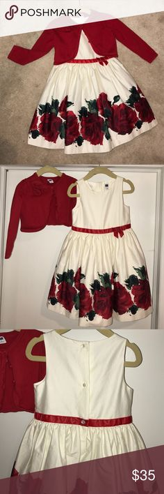 Girls Janie and Jack Red Rose Dress & Cardigan Stunning Janie and Jack ivory dress with vibrant red roses along the bottom and a red velvet ribbon around the waist. Tulle underneath. Selling with cropped red rosette cardigan. Looks beautiful together with ivory tights and red patent leather shoes! Janie and Jack Dresses Formal