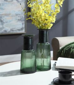 Handcrafted, these vases feature a beautiful ribbed body in a translucent green hue. Adding contrast to the design, the tall necks are accentuated with a rustic iron band. Bring a touch of timeless elegance to your living space with the Castille green glass vases. Small Glass Vases, Wholesale Home Decor, Green Home Decor, Ceramic Table, Garden Accessories, Timeless Elegance, Vases Decor, Urn, Contrast