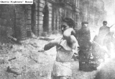A Jewish woman fighter who fell captive to the Germans in the Warsaw ghetto uprising, ordered to strip, to prove that no weapons are concealed on her person. Photographed during the suppression of the Warsaw ghetto uprising in April - May 1943.