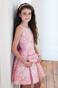 Presenting this pink dream prom dress for girls from David Charles' latest collection. Pair a soft shade of pink with a contrasting floral print and the result is this truly elegant prom dress. Whether your girl needs a dress to make a statement this spring, or you're looking for a birthday gift idea for her, you'll love the retro meets contemporary style of our evening dresses. This wardrobe staple includes a delicate pearl waist belt which transforms into a pink satin ribbon at the back of…