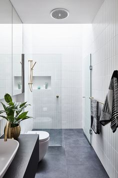 In this modern bathroom, floor-to-ceiling white tiles cover the walls, while a skylight adds natural light to the space. #ModernBathroom #BlackAndWhite #BathroomDesign