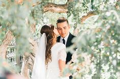 A tree's blurred foliage and branches make the perfect frame, allowing for a peek at a tender moment.Related: 75  New Must-Have Photos With Your Groom