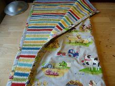 Babytæppe med bomuldsstof på den ene side og strik i uld/bomuld, på den anden. Der er syet punkter rundt omkring, så det ikke buler.