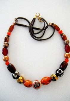 Shades of orange, brown, gold and copper beaded necklace with suede accents, great earth tone colors by mscenna