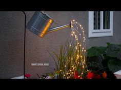 Glowing Watering Can with Fairy Lights - How neat is this? It's SO EASY to make! Hanging watering can with lights that look like it is pouring water. For the full directions and where to buy the lights, visit Smart School House