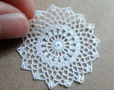 One Miniature crochet white doily handmade with viscose embroidery thread and a tiny hook. This doily will give a romantic touch to you dollhouse, perfect for 1:12 scale, the stitches are so small that it can also be used in 1:24 scale.  It has a diameter of 5.0 cm (1 15/16 inches).  Each doily is washed after finished and blocked with a lot of pins in a flat surface, it will lie flat on your miniature table allowing for cups or flower arrangements to sit and look true to scale. It also ...