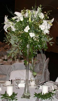 White casablanca lilies with lisianthus and wax flower in an Eiffel Tower vase