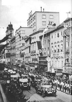 Linz. Hitlers Fahrten im offenen Wagen werden als Triumphzug inszeniert: Fahnen, jubelnde Massen, HJ als Ordner.