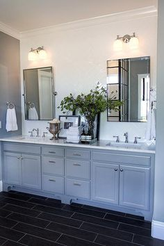 Fabulous bathroom features an accent wall lined with white subway tiled backsplash laid out in a herringbone pattern lined with a gray dual vanity topped with white marble under Pottery Barn Kensington Pivot Mirrors illuminated by Mercer Double Sconces alongside a dark tiled wood like floor.
