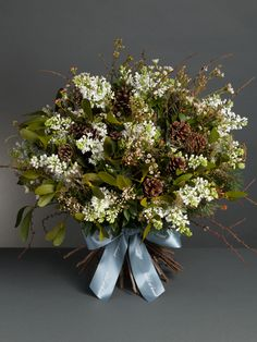 Pine Forest Bouquet - Inspired by a winter woodland, this beautiful bouquet is made up of wax flower, white lilac, pine cones, litchen, mistletoe, pine and seasonal foliage. wildatheart.com