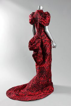 * Alexander McQueen feather-weave gown, probably pre-collection, Autumn-Winter 2009, labelled and size 44, the princess-line gown with seams radiating from the high neck which traverse the hips and meet at the centre back, culminating in a large swagged bustle, the skirt narrowing again before finishing with a fish-tail hem, together with matching clutch bag