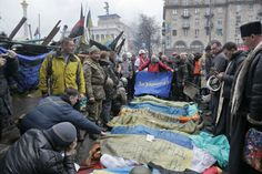 Activists and priests pay respects to protesters who were killed in clashes with police Thursday in Kiev's Independence Square, the epicente...