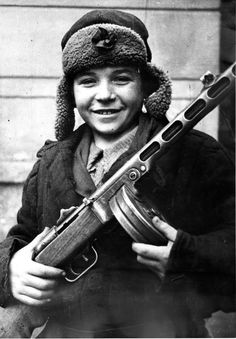 A child soldier for the Red Army. Armed with the standard issue PPSh sub machine gun, he proudly poses for the photographer, 1943.