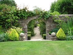 Lovely wall and arch in back yard to walk into garden then follow the path throw the woods then there is the horse barn DREAM!!!!!!!!!
