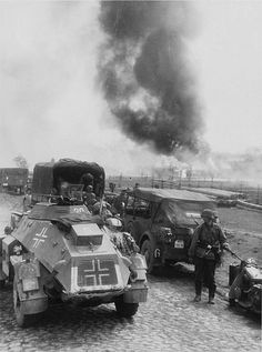 """""""Das Reich"""" recon troops near a burning village. In the foreground is an SdKfz. 221."""