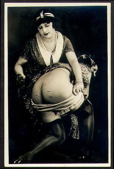 Rare photograph by Grundworth, Paris circa 1925. Erotic lesbian tableaux; mistress with lash, her submissive with skirt up and panties pulled down; silk stockings, garter belt.