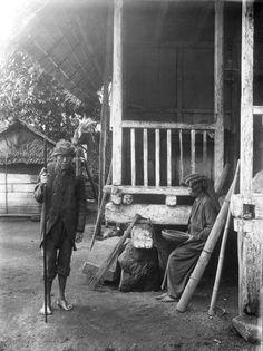 Priester (walian) en een vrouw in een dorp in de Minahasa. Ca 1900