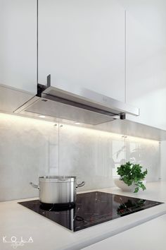 Minimalist white kitchen visualization with Teka products - black induction cooktop and under-cabinet extractor hood, during work.