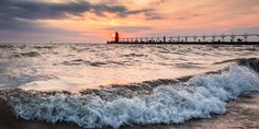 A seascape on high tide with a small silhouetted figure of a lighthouse on a beautiful sunset on the background stock image