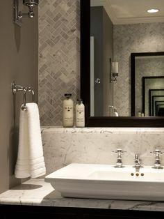 "herringbone wall tile, gorgeous marble counter, dark charcoal walls, wonderful ""jewelry"" fixtures!"