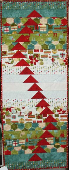 Flying geese and strips:  Come Fly With Me table runner, in Christmas fabric, spotted at Tennessee Quilts