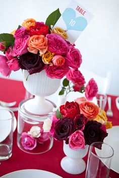 A few - very few - deep purple and antique red roses act as the black to the white vases here. So all the pink and orange roses need to do here is pop pop pop!