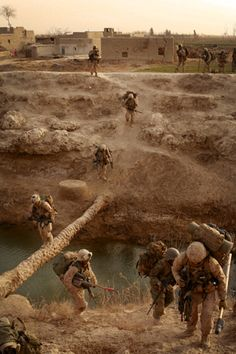 U.S. Marines with Echo Company, 2nd Battalion, 1st Marine Regiment (2/1), Regimental Combat Team 1, and Afghan National Army (ANA) soldiers cross a makeshift bridge during Operation Godfather in Durzay, Afghanistan, Jan. 14, 2011.