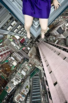 Photographer Jun Ahn, from Seoul, South Korea, has travelled to the top of some of the tallest buildings in her native city, New York and Hong Kong. Once she has climbed to the top of one she will find a suitable location, sit or stand dangerously close to the edge and pose for self portrait photographs. - Picture:  Jun Ahn / Barcroft Media