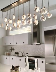 #Kitchen #lighting idea: The elongated shape of LBL Lighting's Bling chandelier makes it perfect for hanging over a kitchen island, while suspended discs of transparent crystal with sandblasted metal accents add a touch of its namesake sparkle. www.lbllighting.com